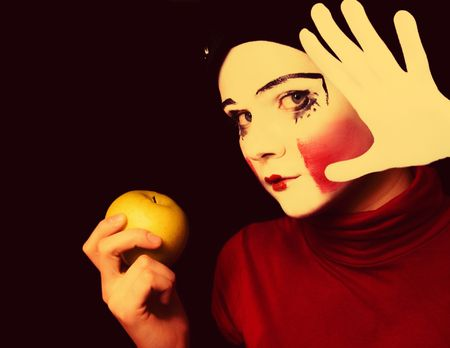 Portrait of the sad mime with an apple on a black background photo