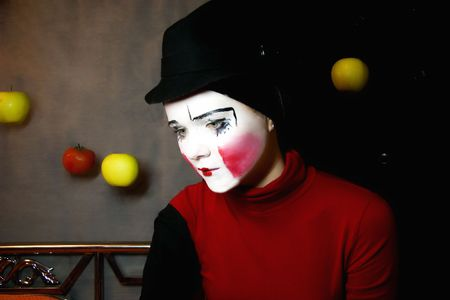 Portrait of the sad mime in a hat with apples photo