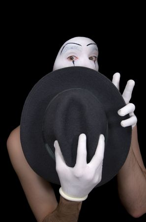 'hide out': Surprise mime with a hat on a black background Stock Photo