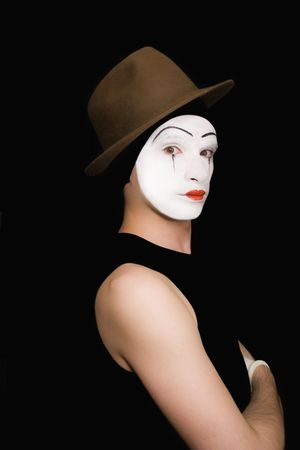 'hide out': Portrait of the mime in a hat on a black background Stock Photo