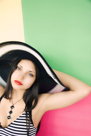 The beautiful girl in a hat on a colour background photo