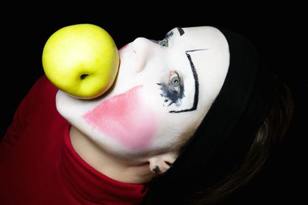 mime biting an apple on a black background Stock Photo - 5420097