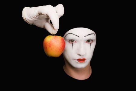m�mica: Retrato de Mime con manzana roja sobre fondo negro Foto de archivo