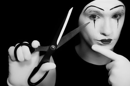 Portrait of  mime with scissors on  black background photo