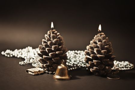 Two candles as a candle with christmas-tree decorations on  black background photo