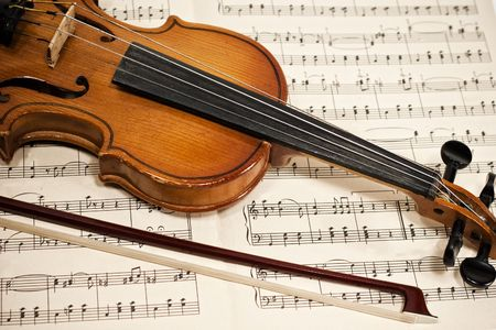 arts: Old violin and bow on musical notes close up