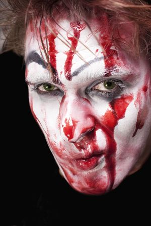 face close up: Malicious green-eyed mime with blood on face close up