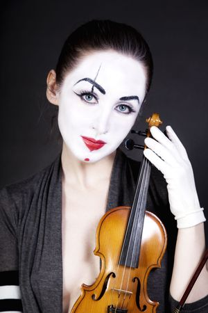 woman  mime with  old violin on  black background photo