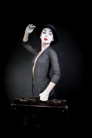 ridicolo: donna MIMO nel cappello con la valigia su sfondo nero