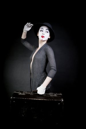 woman  mime in  hat with  suitcase on  black background