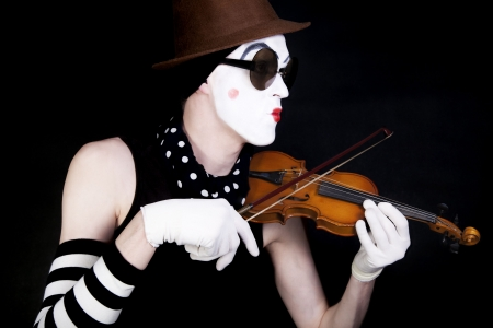 mime playing on small violin in sunglasses on black background photo