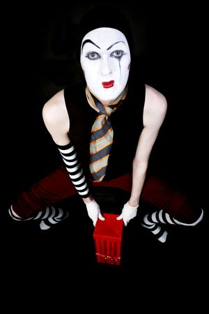 portrait of mime with  red gift box on black background photo
