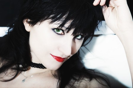 young woman's face with black hair, red lips and green eyes Stock Photo - 6952011