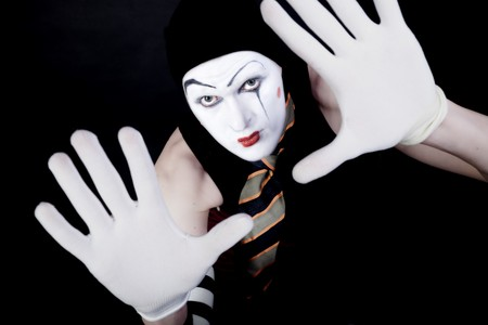 portrait of mime in white gloves on black photo