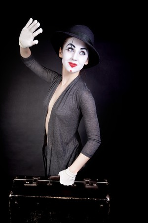 Female mime in white gloves with a suitcase, waving goodbye on a black background photo