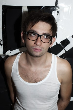 hairy chest: portrait of a young brunette guy in stylish glasses and a white T-shirt