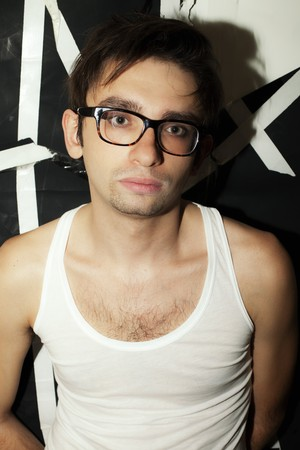 portrait of a young brunette guy in stylish glasses and a white T-shirt photo