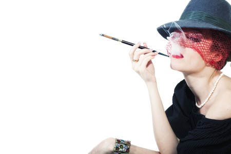 Young beautiful woman with cigarette in mouthpiece in  hat with veil on light background photo