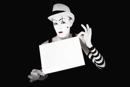 Funny mime in striped gloves and hat, holding a white  blank on a black background