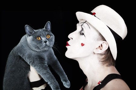 Mime in a white hat holding a gray cat British photo