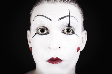 mime face with a theatrical makeup on black background photo
