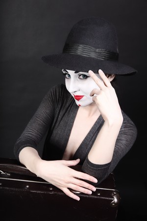 Female mime artist with theatrical makeup in hat and with suitcase photo