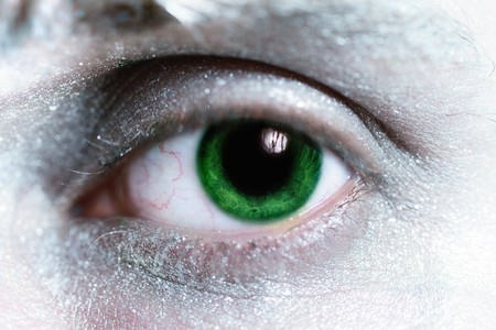 beautiful man green eye  with bright make-up around  closeup photo