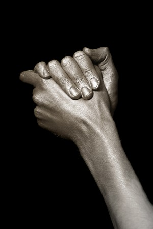 beautiful mans hands in bronze paint isolated on a black background photo