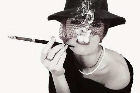 Jonge mooie vrouw met sigaretten in de mond stuk in de hoed met sluier  Stockfoto
