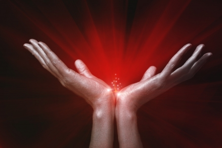 Silver mens hands holding red magic glow on black background photo