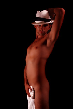 Young beautiful slim stripteaser man in a white hat on a black background Stock Photo - 7564429