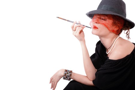 Young beautiful woman with cigarette in mouthpiece in hat with veil isolated on light background photo
