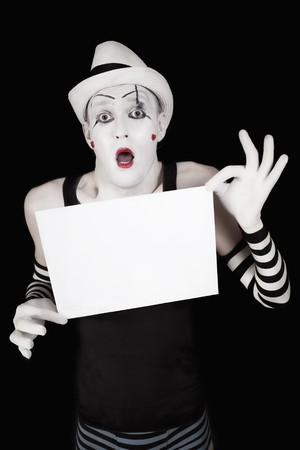 Ape mime in striped gloves and hat, holding a white blank