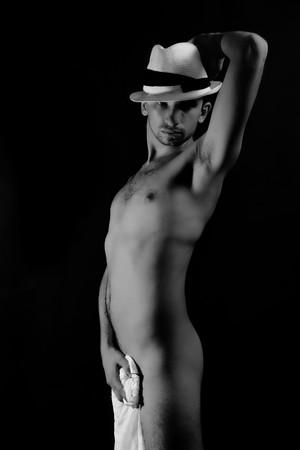 homme nu: Jeune homme nu belle dans un chapeau sur un fond noir  Banque d'images