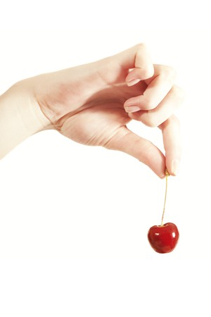 women's hand: cherries in the womens hand isolated on white background