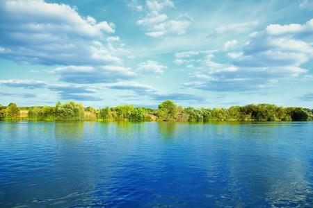 oever van rivier met groene bomen op zomer dag Stockfoto