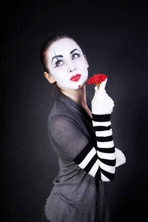 woman mime with theatrical makeup and red flower in hands on black background