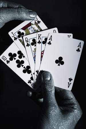 Metal mens hands with playing cards on a black background