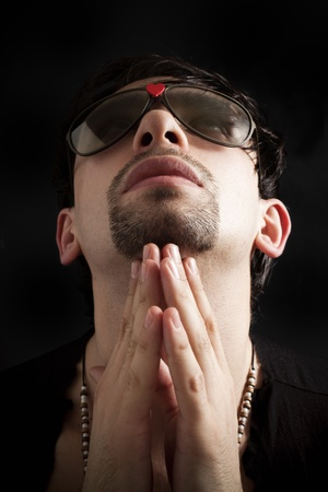 Portrait of young man praying in sunglasses photo