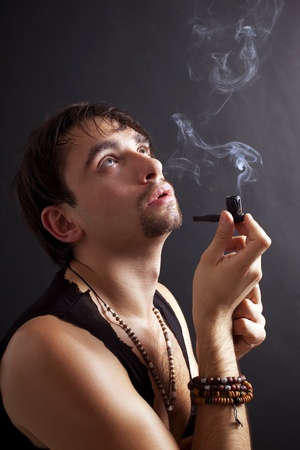 young man smoking  little pipe on black background photo