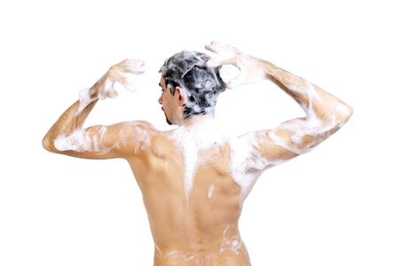 Young naked man taking a shower in foam with beautiful body isolated on white background Stock Photo