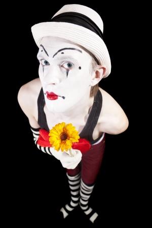 Grappige mime in witte hoed met een boeket van bloemen op een zwarte achtergrond