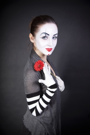 mime: Woman pantomime with a red flower on a black background
