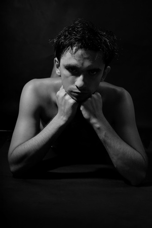 Nude young handsome man on black background photo