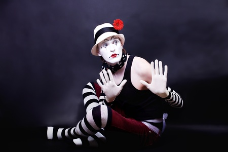 par: Theatrical mime in white hat with red flower sits on the floor Imagens