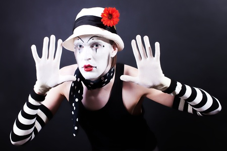 Funny mime in white hat with red flower on a black background