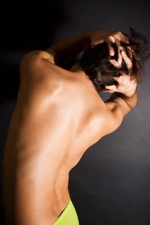 naked tanned young men back on black background photo