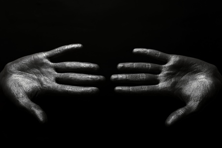 beautiful male hands in silver paint on black background photo