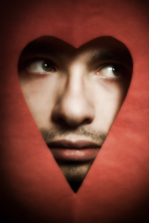 heart shaped: Face of young man peering from hole in heart-shaped