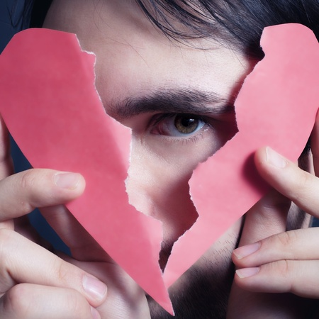 Face of young handsome man with broken paper heart closeup Stok Fotoğraf